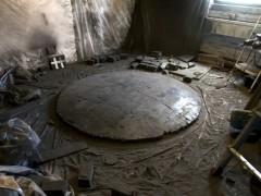 En el piso: Convex Coal Mirror, 2012, carbón, 72 x 72 x 8 pulgadas.