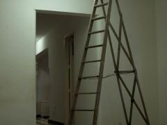 El tubo fluorescente de una sala atrancado contra la pared con una escalera