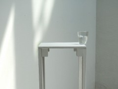Un baso de agua puesto sobre el borde de una mesa
